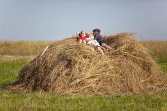 Дети отдыхая в сене Стоковая Фотография