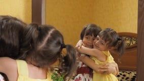Дети перед зеркалом Сестры обнимают Маленькие девочки перед зеркалом сток-видео