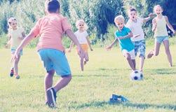 Дети пиная футбол в парке Стоковая Фотография