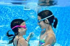 Дети плавают в бассейне подводном, счастливые активные девушки имеют потеху под водой, фитнесом детей и спортом стоковое изображение rf