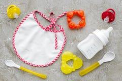 Дети подавая с формулой грудного молока или младенца напудрили молоко и игрушки младенца на сером взгляд сверху предпосылки Стоковые Фото