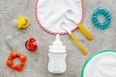 Дети подавая с формулой грудного молока или младенца напудрили молоко и игрушки младенца на сером взгляд сверху предпосылки Стоковая Фотография RF