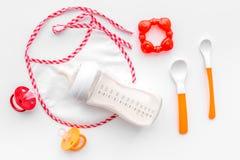 Дети подавая с формулой грудного молока или младенца напудрили молоко и игрушки младенца на белом взгляд сверху предпосылки Стоковое Изображение