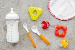 Дети подавая с формулой грудного молока или младенца напудрили молоко и игрушки младенца на сером взгляд сверху предпосылки Стоковое Фото