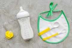 Дети подавая с формулой грудного молока или младенца напудрили молоко и игрушки младенца на сером взгляд сверху предпосылки Стоковое Изображение RF