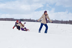 дети помогающ саням riding мати их Стоковая Фотография
