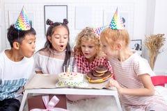 Дети помогая их другу дунуть вне candels стоковые изображения