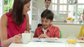 Дети порции матери с домашней работой как отец используют компьтер-книжку акции видеоматериалы