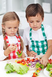 Дети подготавливая закуску овощей в кухне Стоковая Фотография