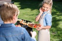 Дети подготавливая мясо и овощи на барбекю жарят outdoors Стоковые Изображения