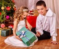 Дети получая подарки под рождественской елкой Стоковые Фотографии RF