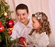 Дети получая подарки под рождественской елкой Стоковое Изображение