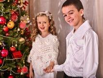 Дети получая подарки под рождественской елкой Стоковая Фотография