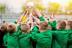 Дети празднуя победу футбола Молодые футболисты держа трофей стоковое фото rf