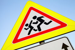 Дети предосторежения, поднимающее вверх дорожного знака близкое Стоковые Изображения