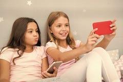 Дети принимая selfie в спальне r Детство Girlish отдыха счастливое Волосы девушек длинные со смартфонами стоковые изображения