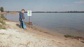 Дети против погани, мальчика ребенк вытягивают тяжелую сумку погани на указывать знак на обваловке реки после очищать вверх пласт акции видеоматериалы