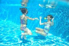 Дети плавают в бассейне подводном, счастливые активные девушки имеют потеху под водой Стоковая Фотография