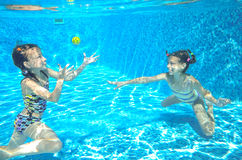 Дети плавают в бассейне подводном, счастливые активные девушки имеют потеху под водой Стоковые Фото