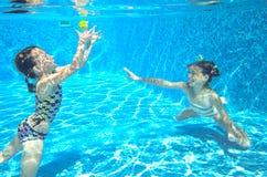 Дети плавают в бассейне подводном, счастливые активные девушки имеют потеху под водой Стоковое фото RF