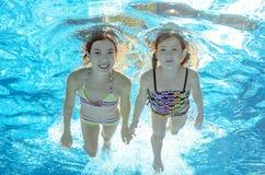 Дети плавают в бассейне под водой, девушки имеют потеху в воде Стоковое фото RF