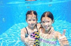 Дети плавают в бассейне под водой, девушки имеют потеху в воде, Стоковое Изображение