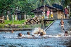 Дети племени людей Asmat купают и плавают в реке Стоковые Изображения RF