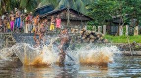 Дети племени людей Asmat купают и плавают в реке Стоковое фото RF