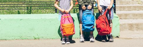Дети различных возрастов, мальчиков и девушек держат яркие рюкзаки r r r стоковые фото