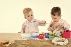 дети рисуют Пасха, дети в ушах зайчика, братья с яичками Стоковые Фото