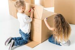 Дети рисуя на картонной коробке Стоковое фото RF