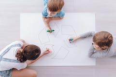 Дети рисуя плакат стоковые фото