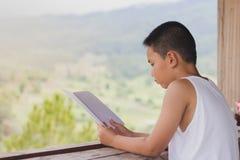 Дети сидят книги чтения для того чтобы найти знание дома стоковое фото