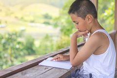 Дети сидят книги чтения для того чтобы найти знание дома стоковая фотография