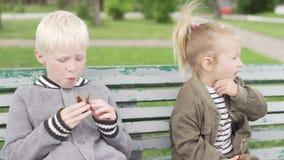 Дети сидят на стенде в парке видеоматериал