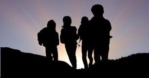 Дети силуэта на горе против неба Стоковые Фотографии RF