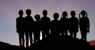 Дети силуэта стоя в строке против неба Стоковые Изображения RF