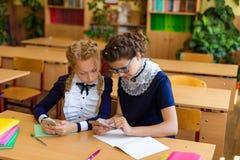 Дети сидят в телефонах на уроках Стоковая Фотография RF