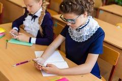 Дети сидят в телефонах на уроках Стоковое фото RF