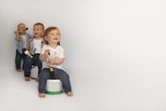 Дети сидят на больших чонсервных банках краски стоковые фотографии rf
