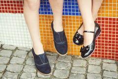 Дети сидят, ноги качая в красивых новых ботинках стоковые фотографии rf