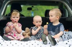 Дети сидя в багажнике автомобиля 3 дет едят конфеты Стоковая Фотография RF