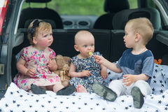 Дети сидя в багажнике автомобиля 3 дет едят конфеты Стоковая Фотография