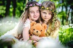 Дети сидя в луге Стоковое Изображение