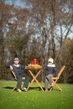 Дети сидя на деревянном столе на пикнике Стоковое Фото