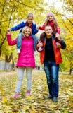 Дети сидя на плечах родителей в осени Стоковые Фото