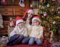 Дети сидя с матерью под рождественской елкой в шляпах Стоковое Фото