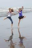 Дети скача на пляж Стоковые Изображения