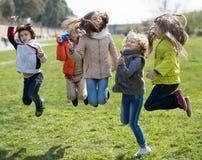 Дети скачут вверх на лужайку в парке Стоковые Изображения