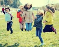 Дети скачут вверх на лужайку в парке Стоковое фото RF